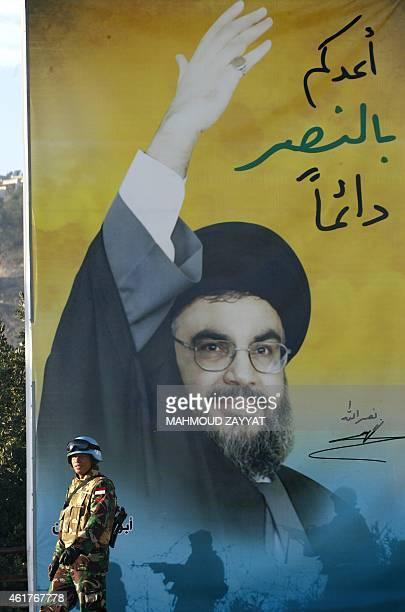 A peacekeeper of the United Nations Interim Force in Lebanon stands next to a billboard bearing a portrait of Hezbollah chief Hassan Nasrallah during...