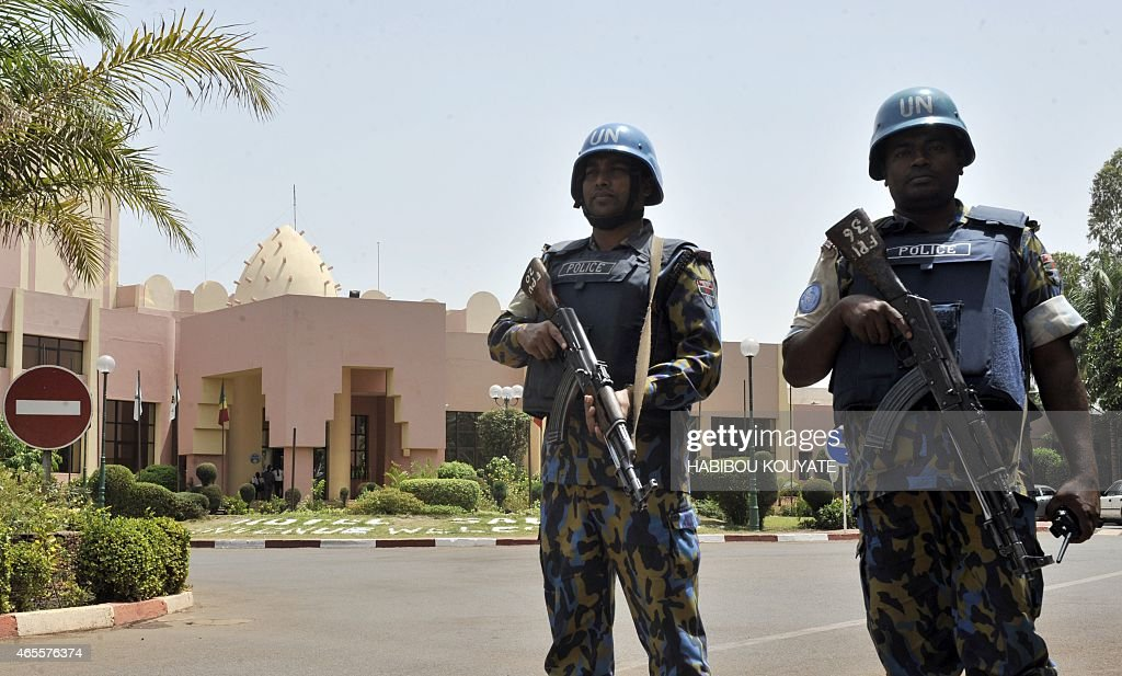UN peacekeeper police officers stand guard at entrance of Hotel Salem in Bamako on March 8 2015 Two civilians and a UN peacekeeper were killed as...