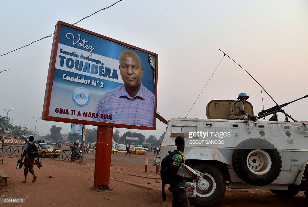 A UN peacekeeper sits on an armoured vehicle beside a campaign posters of Central African Republic second round presidential candidate Faustin Archange Touadera in Bangui on February 10, 2016, ahead of the Febuary 14 presidential and legislatives elections. The deferred presidential run-off, delayed due to organisational problems, and postponed legislative election, rescheduled after annulment due to irregularities, have been widely seen as turning a page on the worst sectarian violence in the traditionally unstable and dirt poor nation. / AFP / ISSOUF SANOGO