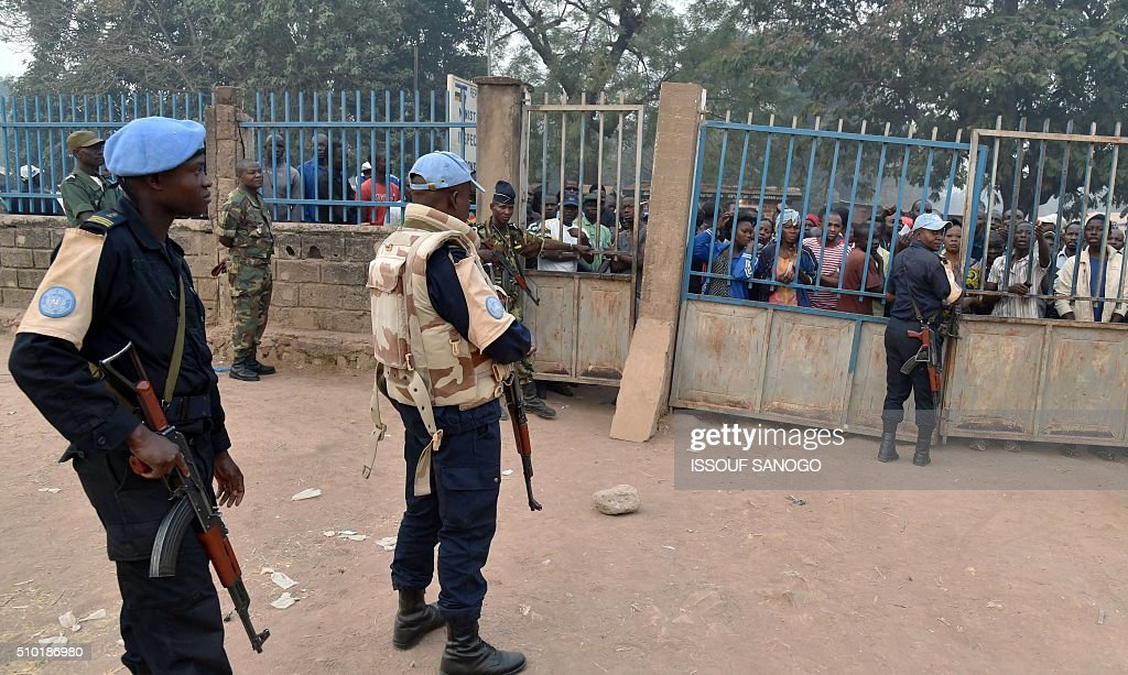 UN peacekeepers stand guard as voters wait outside for the opening of polling stations in Bangui, on February 14, 2016, as people go to the polls to take part in the country's delayed legislative and presidential elections. The Central African Republic holds delayed presidential and parliamentary polls on February 14, with voters desperate to usher in peace after the country's worst sectarian violence since independence in 1960. / AFP / ISSOUF SANOGO