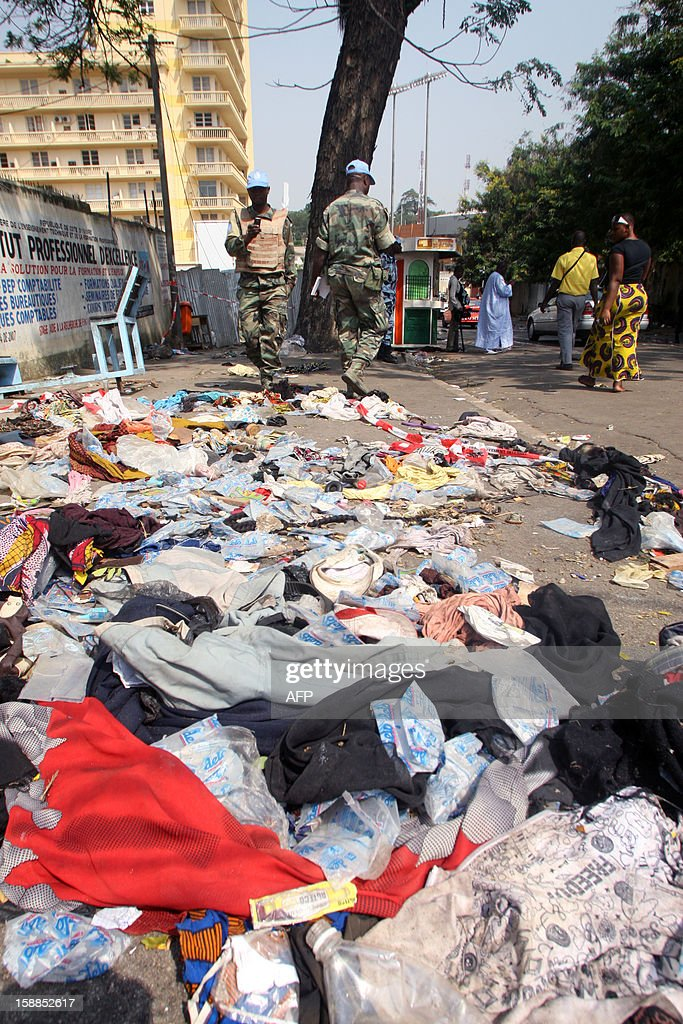 UN peacekeepers stand next to shoes and various items lying on the pavement at the scene of a stampede, on January 1, 2013. At least 60 people died and at least dozens were injured as crowds stampeded overnight during celebratory New Year's fireworks, Ivory Coast rescue workers said on January 1, 2013. AFP PHOTO/HERVE SEVI