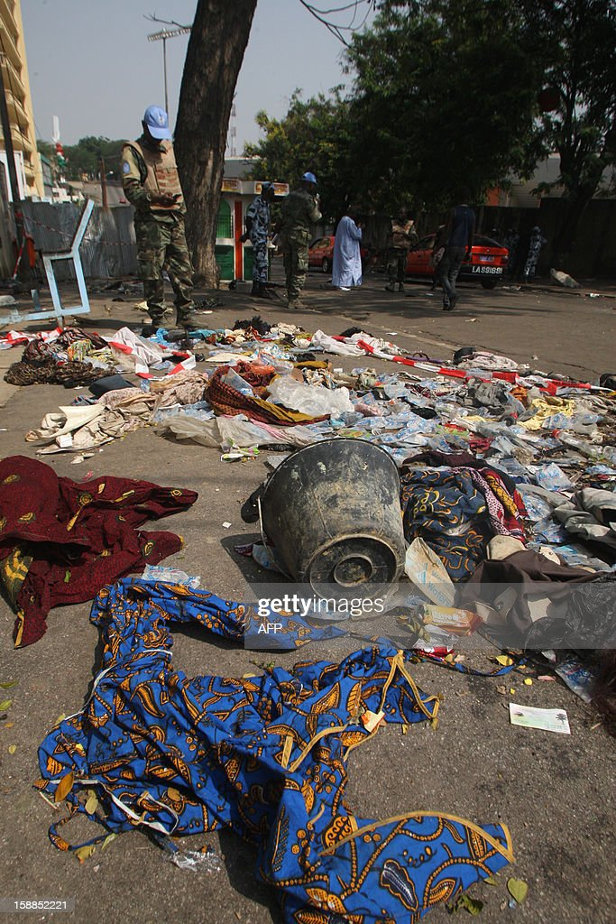 UN peacekeepers stand on a street in Abidjan as shoes and various items are seen on the pavement at the scene of a stampede, on January 1, 2013. At least 60 people died and at least dozens were injured as crowds stampeded overnight during celebratory New Year's fireworks, Ivory Coast rescue workers said on January 1, 2013. AFP PHOTO/HERVE SEVI