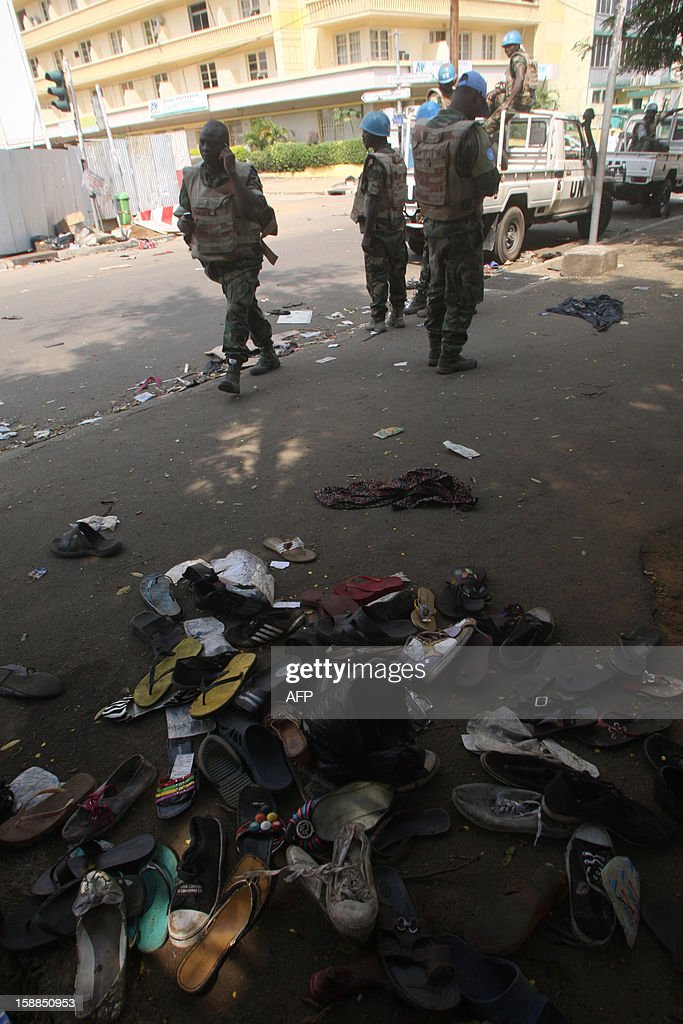 UN peacekeepers stand on a street in Abidjan as shoes are seen on the pavement at the scene of a stampede, on January 1, 2013. At least 60 people died and at least dozens were injured as crowds stampeded overnight during celebratory New Year's fireworks, Ivory Coast rescue workers said on January 1, 2013. AFP PHOTO/HERVE SEVI