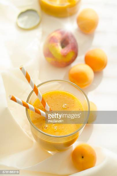 Peach apricot smoothie in glass, drinking straws