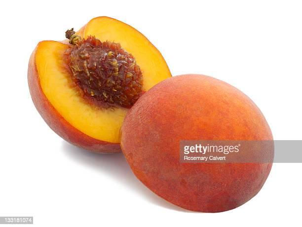 Peach cut in half to reveal stone inside.