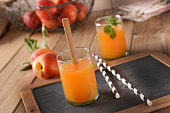 Peach drink with mint leaves in the glass - closeup