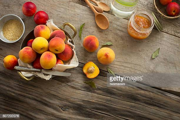 Peaches on moody rustic wooden kitchen table top background.