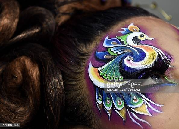 A peacock is seen painted around a model's eye during a hairstyling and makeup competition in Kuala Lumpur on May 18 2015 Professional hairdressers...
