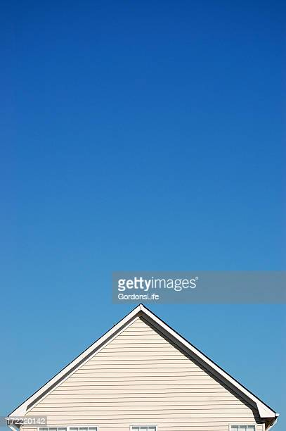 Peak of a house against a clear blue sky