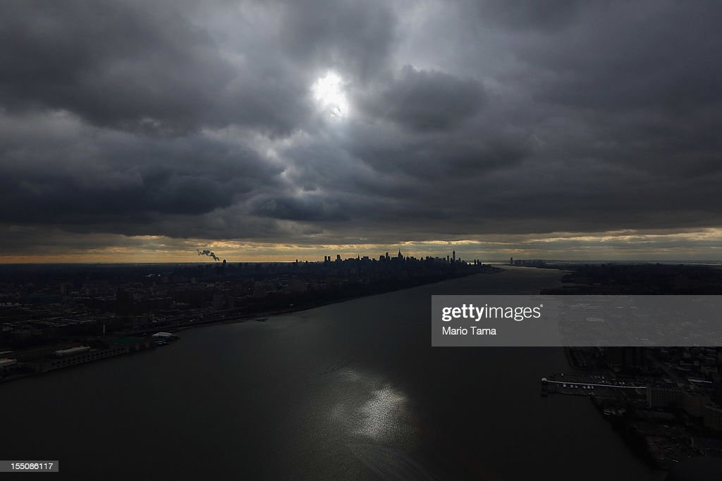 A peak of sun shines down on the Hudson River through the clouds with the Manhattan skyline in the distance after Superstorm Sandy on October 31, 2012 in New York City. At least 50 people were reportedly killed in the U.S. by Sandy. New York City was hit especially hard with widespread power outages and significant flooding in parts of the city.