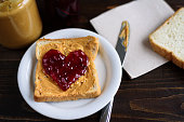 Peanut butter and heart shaped jelly sandwich on wooden background