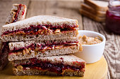 Peanut butter and jelly sandwich with whole wheat bread on rustic wooden table