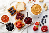 Sandwiches with peanut butter, jam and fresh fruits on white wooden background from top view