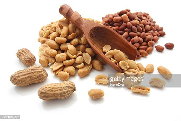 Peanuts, in shell and out, with scoop on a white background