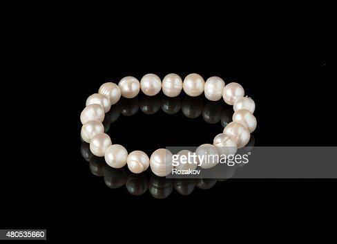 Pearl bracelet on a black mirror surface : Stock Photo