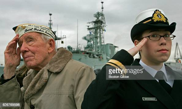 Pearl Harbor survivor Barney Murphy left and Canadian Navy sailor SLT Heather MacDonald hold a salute during a moment of prayer during the annual...