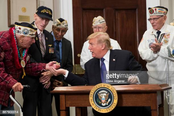Pearl Harbor survivor Larry Parry shows a presidential challenge coin to US President Donald Trump after he signed a proclamation for National Pearl...