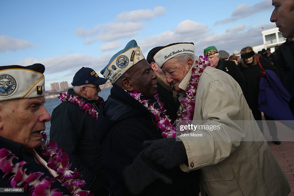 Pearl Harbor survivors embrace at a ceremony marking the 72nd anniversary of the attack on Pearl Harbor, Hawaii on December 7, 2013 in New York City. Four Pearl Harbor survivors from the New York area gathered with former crew members of the USS Intrepid to mark the Japanese surprise attack on December 7, 1941 which killed 2,402 Americans and brought the United States into WWII.