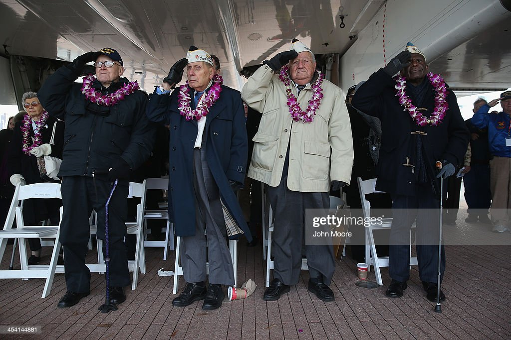 Pearl Harbor survivors salute during the U.S. national anthem at a ceremony marking the 72nd anniversary of the attack on Pearl Harbor, Hawaii on December 7, 2013 in New York City. Four Pearl Harbor survivors from the New York area gathered with former crew members of the USS Intrepid to mark the Japanese surprise attack on December 7, 1941 which killed 2,402 Americans and brought the United States into WWII.
