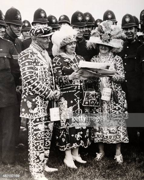 Pearly King and Queens in their traditional regalia watched by a group of policemen attempting to pick a winner at Epsom Racecourse on Derby Day 27th...