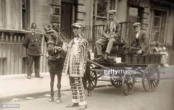 A Pearly King with his mates on a horsedrawn cart watched by a policeman in London circa 1910
