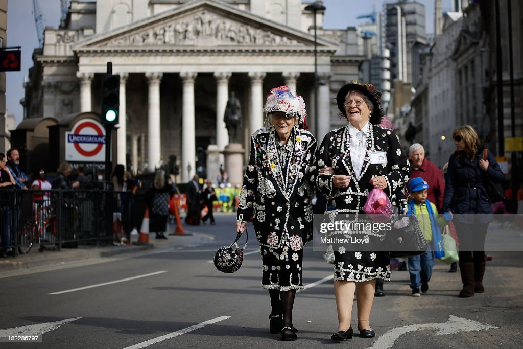 Pearly Kings and Queens process from the Guildhall Yard throught the city of London on September 29, 2013 in London, England. The Harvest Festival features dancing and entertainment by participants in traditional costumes and concludes with a service at St Mary-le-Bow Church, home of the renowned Bow Bells. Dressing as a Pearly King or Queen, by wearing clothes adorned with pearl buttons, originated in the 19th century when London street sweeper Henry Croft decorated his uniform and began collecting money for charity