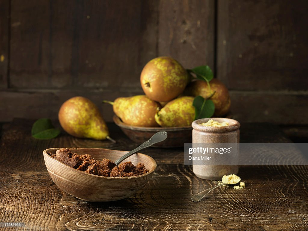 Pears and spiced muscovado sugar and molasses on  rustic wooden surface