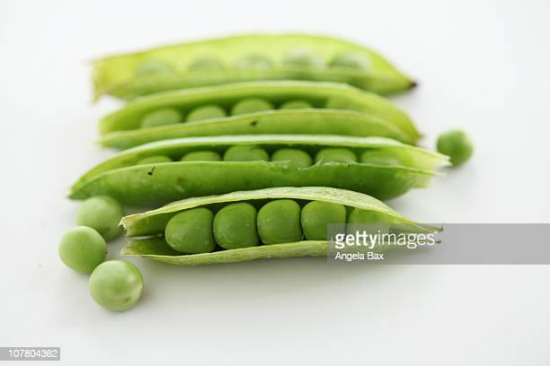 Peas in their pods on white background