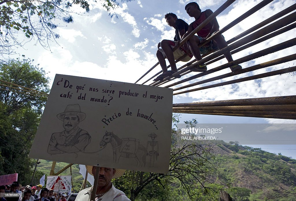 A peasant holds a sign reading 'What is it good for to produce the best coffee in the world? Price of hunger...' during a protest for the difficulties of the coffee sector in Bolombolo municipality, southwest of Medellin, Antioquia department, Colombia on February 25, 2013. Prices and production of coffee have dropped in the last years, informed coffee grower leaders. AFP PHOTO/Raul ARBOLEDA