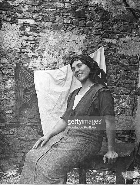 A peasant in Strassoldo seated outdoor on a little table is smiling close to some clothes hanging on a stone wall Strassoldo is a parish of...