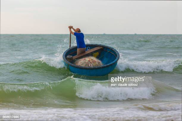 Peasant returning from fishing with a traditional boat, in lagi beach (vietnam)