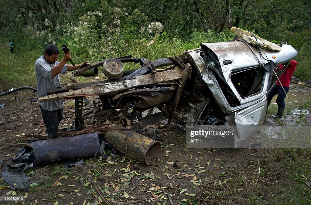 A peasant takes parts out of the remains of a car bomb in El Palo, department of Cauca, Colombia, on February 5, 2013. Two car bombs were detonated allegedly by Revolutionary Armed Forces of Colombia (FARC) guerrillas at a military checkpoint in southwestern Colombia Tuesday, killing a civilian and a soldier, and injuring three soldiers.