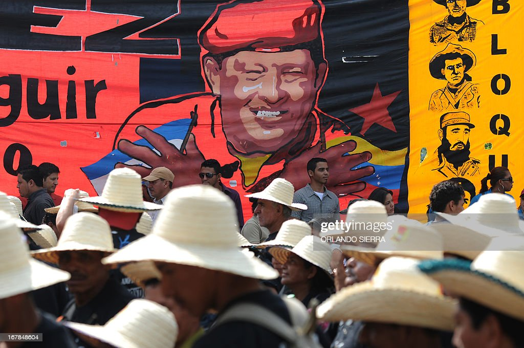 Peasants and workers march in front of a banner showing a portrait of Venezuelan late president Hugo Chavez during a May Day rally in Tegucigalpa on May 1, 2013. AFP PHOTO / Orlando SIERRA