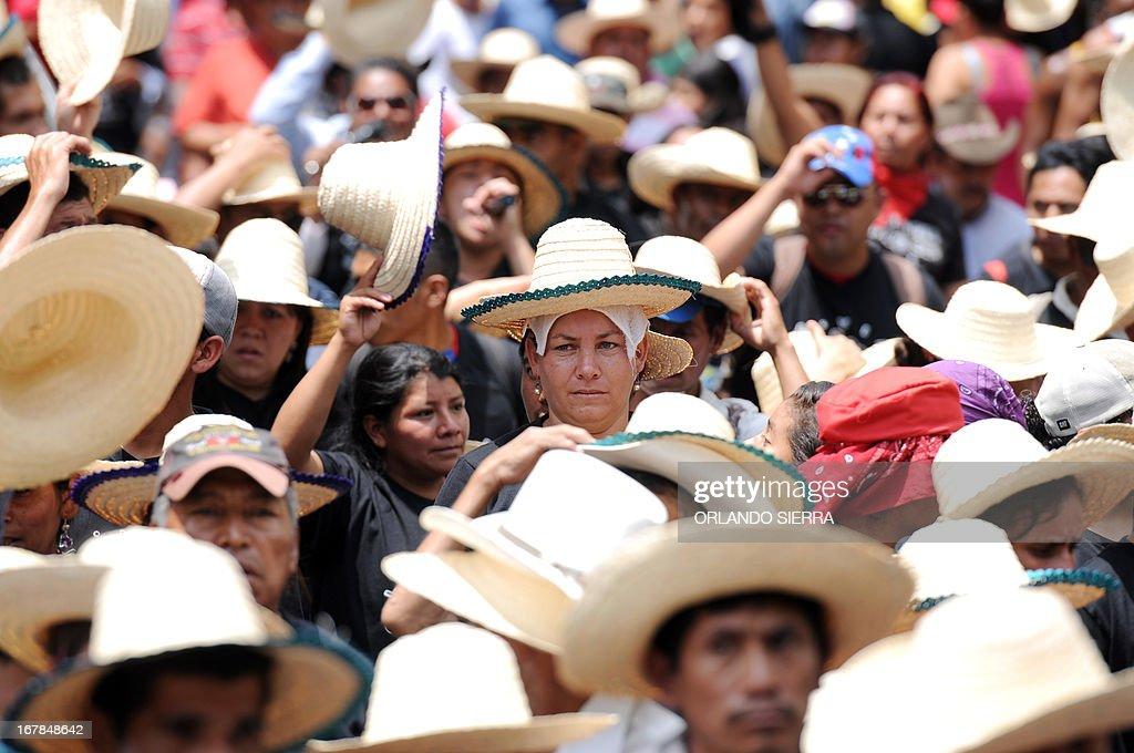 Peasants and workers march in front of a banner showing a portrait of Venezuelan late president Hugo Chavez during Labour Day celebrations in Tegucigalpa on May 1, 2013. AFP PHOTO / Orlando SIERRA