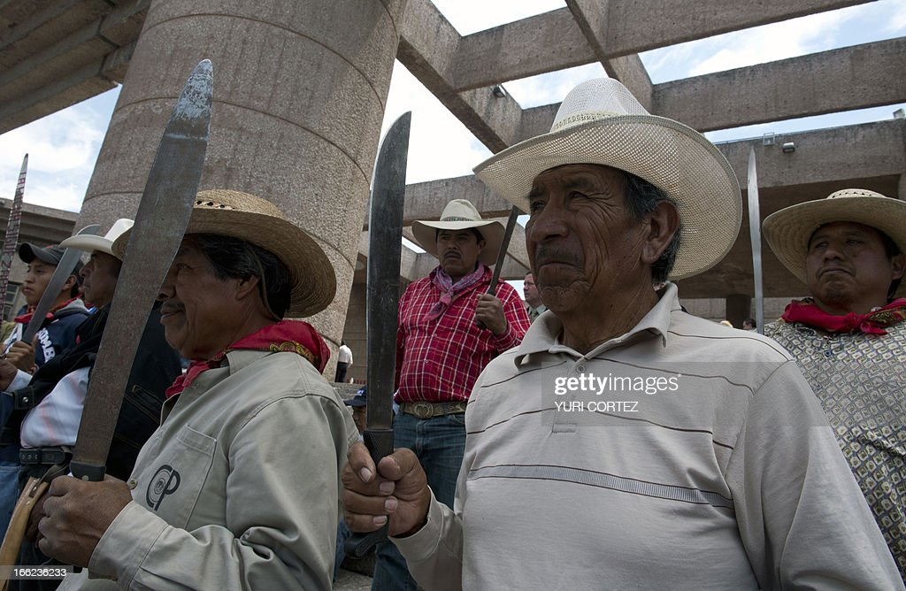 Peasants coming from Salvador Atenco and who support teachers of the National Coordinating Commitee of Education Workers (CNTE) blandish their machetes during a protest in front of the Justice Palace on April 10, 2013 in Mexico City. Teachers protest against the educational reform proposed by the Mexican government. AFP PHOTO / Yuri CORTEZ