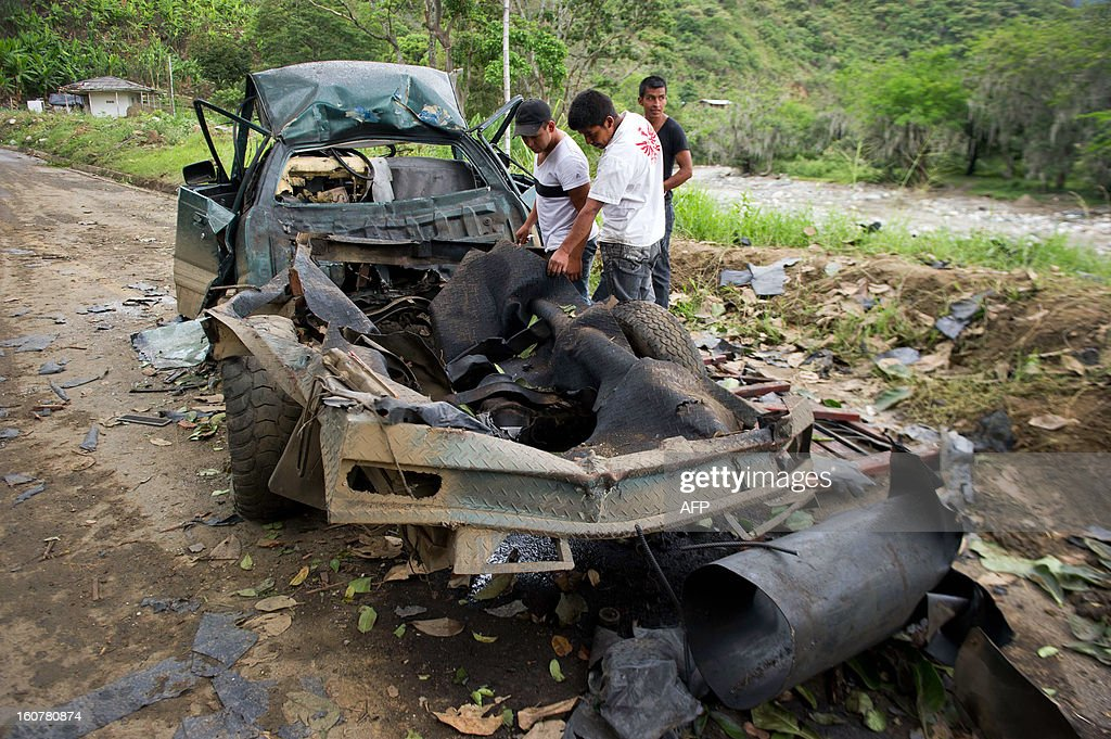 Peasants look at the remains of a car bomb in El Palo, department of Cauca, Colombia, on February 5, 2013. Two car bombs were detonated allegedly by Revolutionary Armed Forces of Colombia (FARC) guerrillas at a military checkpoint in southwestern Colombia Tuesday, killing a civilian and a soldier, and injuring three soldiers.