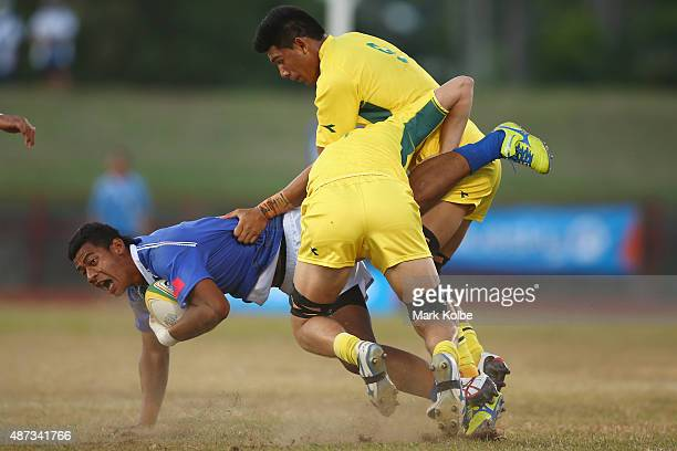 Peato Toeafe of Samoa is tackled during the boys match between Australia and Samoa in the rugby sevens competition at the Apia Park Sports Complex on...
