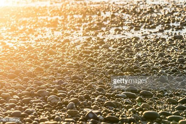 Pebble beach with sun flare