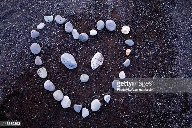 Pebbles arranged in heart shape on black sand