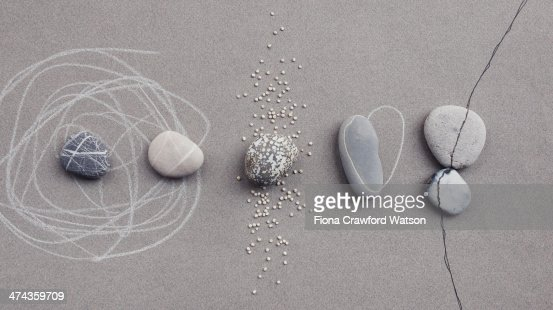 pebbles on grey paper with chalk and ink lines