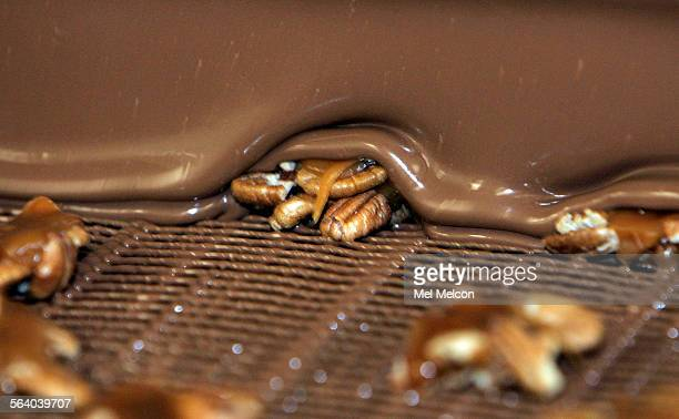 Pecans are dipped in dark chocolate as they make their way along an enrober at See's chocolate manufacturing plant in Los Angeles