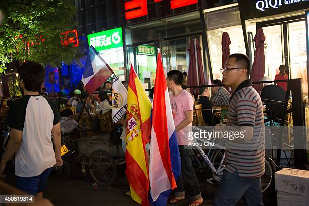 Peddlers sell flags at Beijing Sanlitun Bar Street on June 19 2014 in Beijing China Sanlitun Bar Street is a famous bar street in Beijing people from...