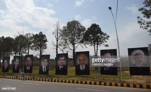 A pedestarian walks past billboards showing leaders Pakistan's Prime Minister Nawaz Sharif Tajikistan's President Emomali Rakhmon Turkish President...