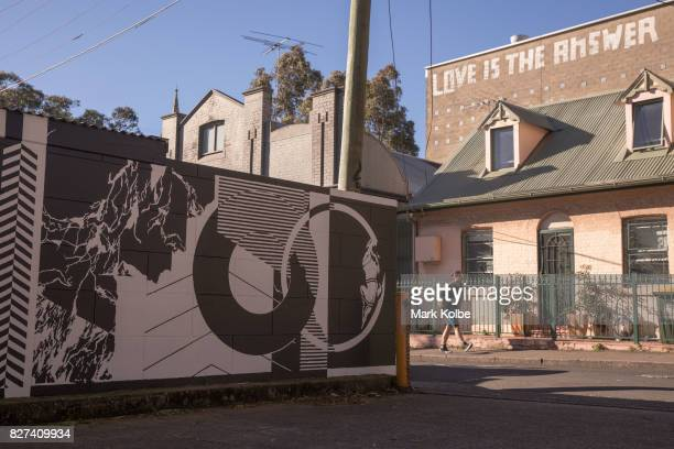 A pedestrain passes near a mural painted on a fence by artist Georgia Hill in Newtown on August 7 2017 in Sydney Australia Perfect Match is an Inner...