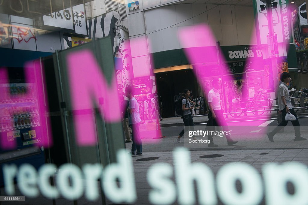 Pedestrains are reflected in the window of the HMV Record Shop operated by Lawson HMV Entertainment Inc. in the Shibuya district of Tokyo, Japan, on Wednesday, Sept. 28, 2016. Spotify Ltd. is bringing its popular online music service to Japan, a large and lucrative market where fans have demonstrated a continuing fondness for CDs and even vinyl records. Photographer: Noriko Hayashi/Bloomberg via Getty Images