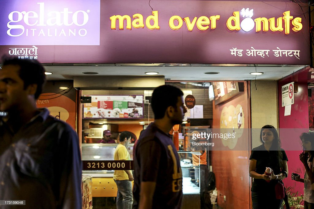 Pedestrains walk past a Gelato Italiano ice cream and Mad Over Donuts store in the suburb of Bandra in Mumbai, India, on Saturday, July 6, 2013. India's consumer price index (CPI) figures for June are scheduled to be released on July 12. Photographer: Dhiraj Singh/Bloomberg via Getty Images