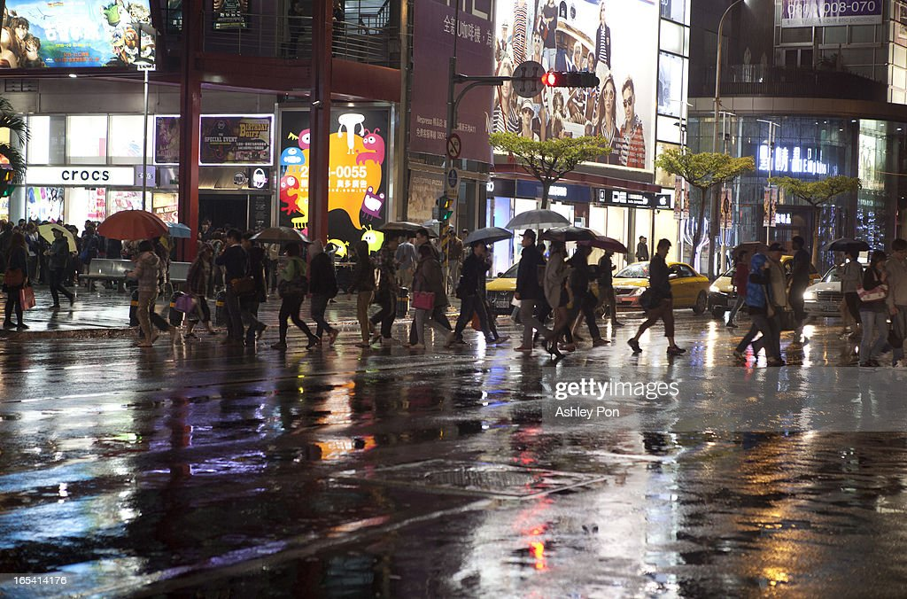 Pedestrains with umbrellas pass a traffic light at night at the shopping distrct in Taipei's Hsin-yi district on April 3, 2013 in Taipei, Taiwan. Franchise and chain operations in Taiwan's retail and food sectors make up 50 per cent of sales, and 25 per cent of the service sector.