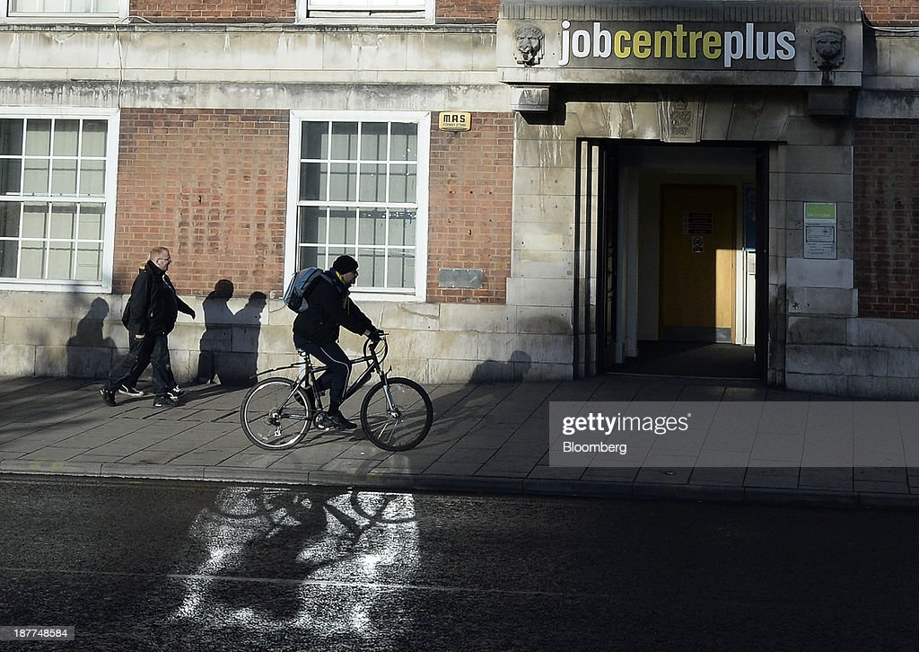 A pedestrian and a cyclist pass the entrance to a job centre in Leeds, U.K., on Tuesday, Nov. 12, 2013. Under Bank of England Governor Mark Carney's forward-guidance policy, the central bank has pledged to not to withdraw stimulus at least until unemployment falls to 7 percent. Photographer: Nigel Roddis/Bloomberg via Getty Images