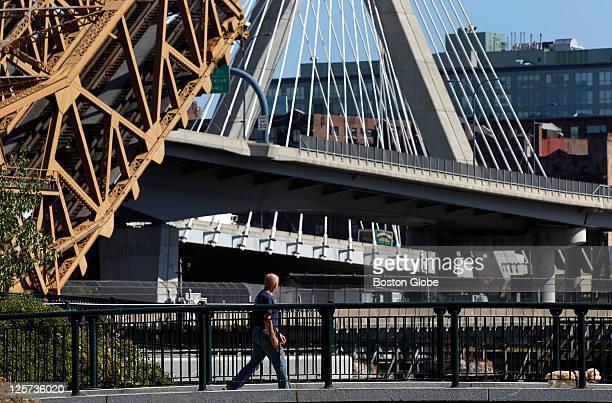 A pedestrian and his dog walk across a small footbridge as the railroad bridge at left goes up with the Leonard P Zakim Bunker Hill Memorial Bridge...