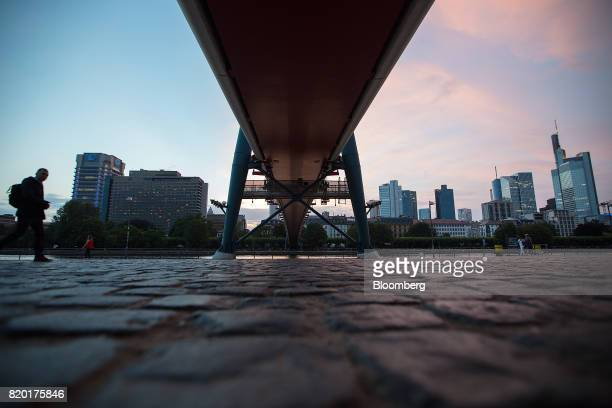A pedestrian approaches a bridge on the River Main at dusk as skyscrapers stand beyond in Frankfurt Germany on Wednesday July 19 2017 Frankfurt has...